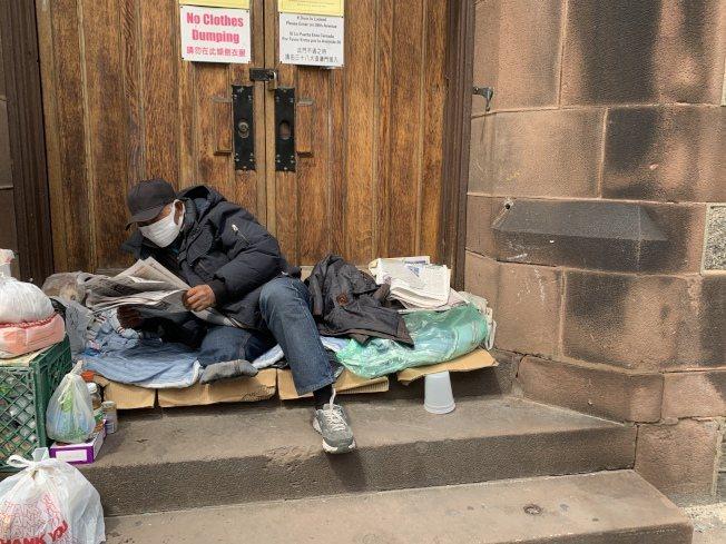 一名華裔遊民在法拉盛教堂前看中文報紙。(記者顏嘉瑩/攝影)