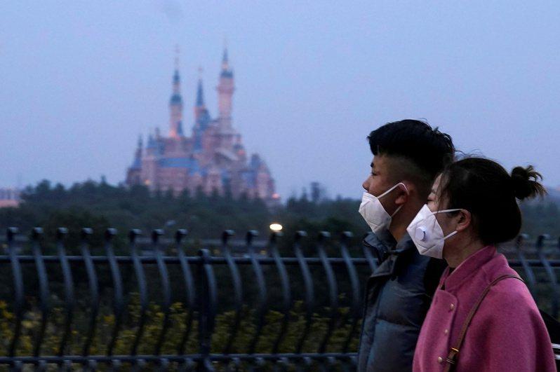 今年1月農曆除夕,戴著口罩的行人走過上海迪士尼樂園之前。  路透