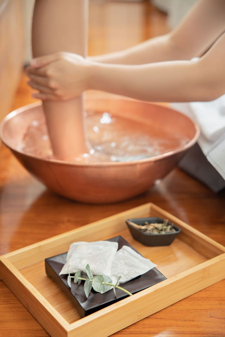 沐蘭SPA芳療師以漢方足浴包放鬆疲憊的雙腳。圖/台北晶華酒店提供