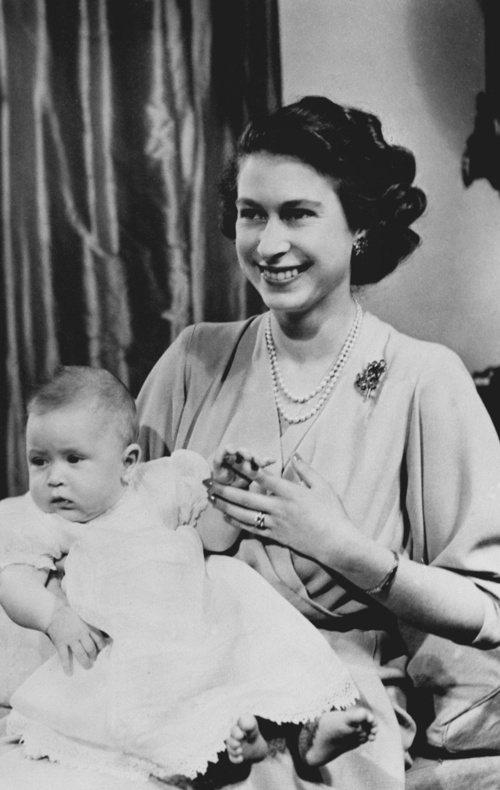 1949年的英國明信片,配戴珍珠串鍊的英女王抱著剛出生的查爾斯王子。 圖/取自R...
