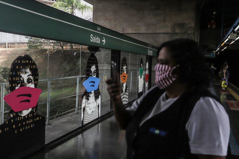 5月6日,在巴西聖保羅市一個地鐵站,一名女子給「戴口罩」的肖像拍照。 為了提醒人們重視新冠疫情,巴西藝術家阿萊士·弗萊明6日給自己創作的這組肖像添加了「口罩」。弗萊明於1998年在這個地鐵站進行了這組人物肖像藝術創作。新華社