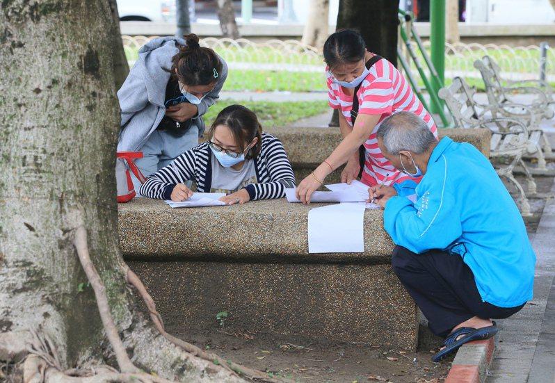 行政院擴大紓困方案申請人潮不斷,有民眾拿著表格跑到公園內蹲坐填寫,希望能順利領到紓困金。 記者潘俊宏/攝影