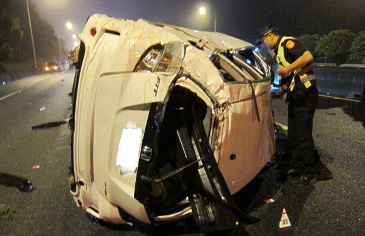 1輛白色轎車行駛國道變換車道不當,撞擊內側護欄後側翻滾,駕駛人被拋出車外死亡。圖/國道警察局提供