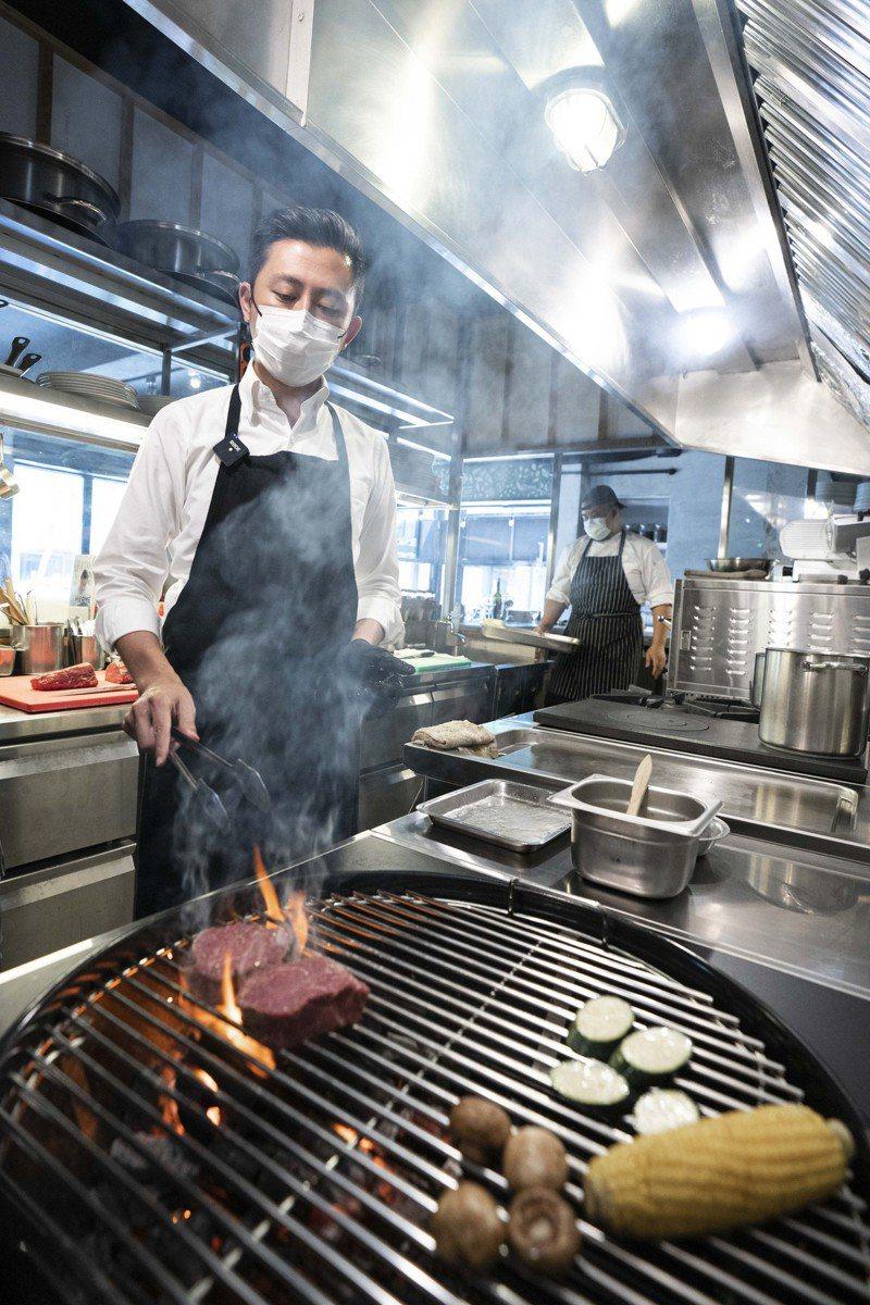 林智堅向主廚請教如何控制牛排火侯、撒調味品與擺盤,煎烤時更是小心翼翼照顧火侯和熟度。記者王駿杰/翻攝