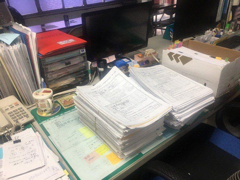 屏東縣各鄉鎮市公所處理紓困補助的承辦人員,假日仍面對堆積如山的申請資料。記者陳弘逸/翻攝