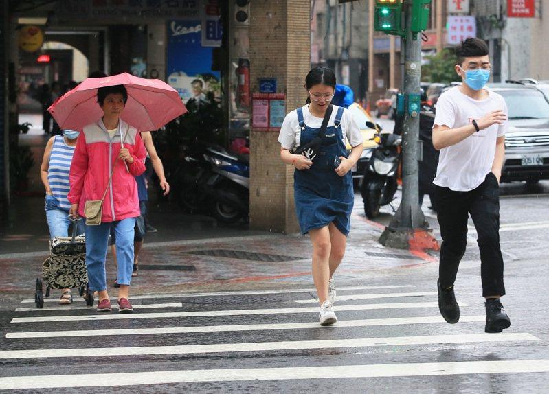 今天天氣炎熱,但下午突然轉陰並降雨,路上許多民眾紛紛快跑避雨。記者潘俊宏/攝影