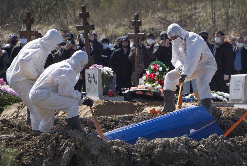 殯葬人員十日在俄國聖彼得堡郊外一處墓地埋葬新冠病毒病故者遺體,死者的親友們隔著安全距離觀看。(美聯社)