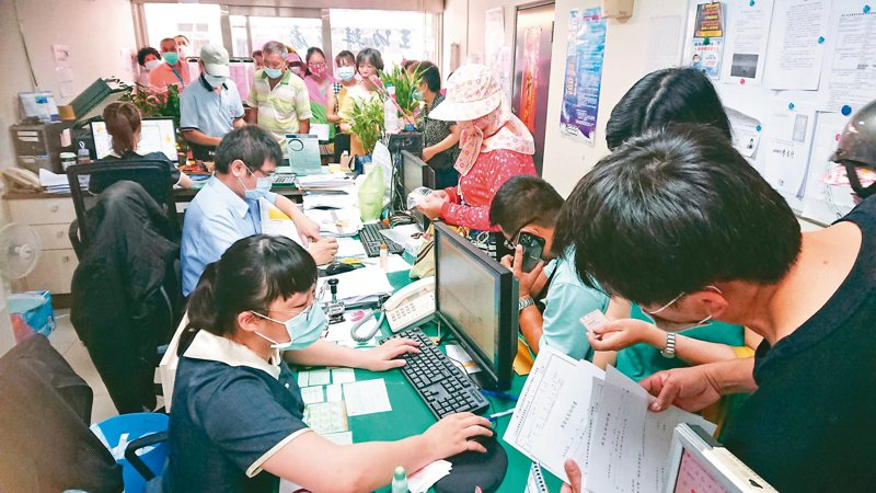 農漁民紓困補助申請昨上路,彰化區漁會王功辦事處擠滿人潮,許多人在辦公室外填寫表格,希望能盡快領到紓困金。 記者簡慧珍/攝影