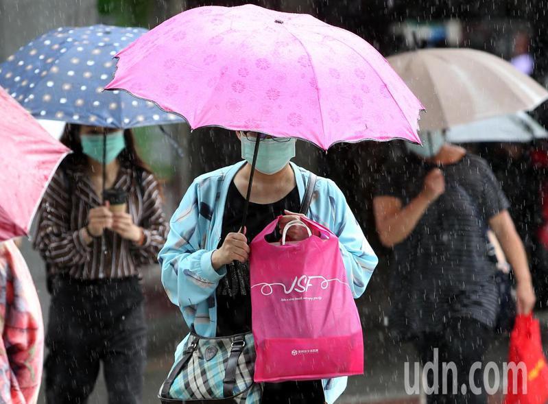夾帶水氣的鋒面上午通過北台灣,民眾在大雨中上班或外出採買。記者侯永全/攝影