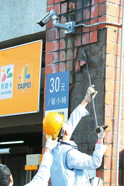 台北幾年前寒流過後後,接連發生多起建物外牆磁磚剝落,一家公有停車場人員敲落有疑慮的磁磚,以策安全。 圖/聯合報系資料照片