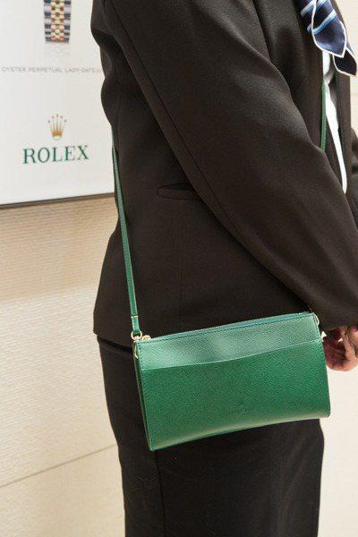勞力士專賣店中,現場服務人員身上的綠色小包,同樣也是同步全球最新規格。 記者陳立...