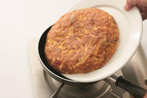 義式蛋包的煎法步驟:讓蛋包從盤子滑進平底鍋。 圖/健行文化