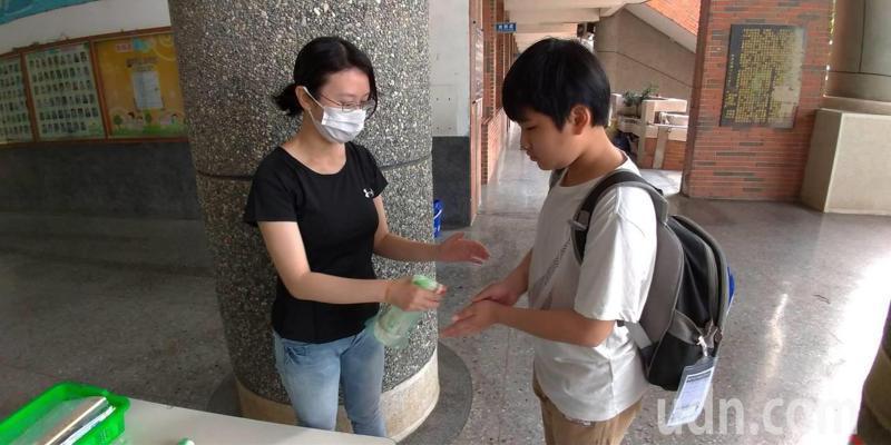 學生上學脫口罩,仍要用酒精消毒。記者魯永明/攝影
