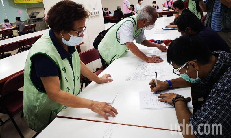 高雄市社會局志工(左穿綠色背心)到區公所協助民眾申請紓困補助。圖/高雄市社會局提供