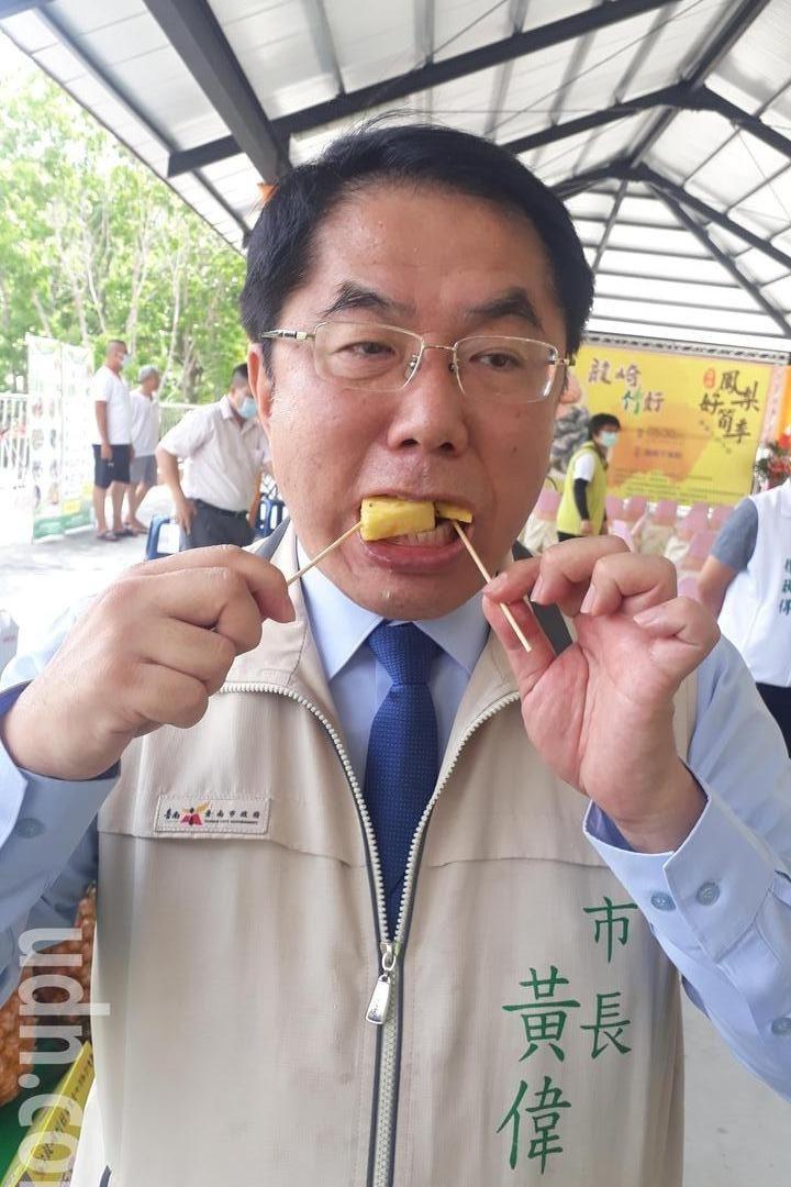 台南市長黃偉哲今天在龍崎區公所舉辦的促銷活動上 大口吃鳳梨,他強調 疫情相關限制何時解封不預設立場。記者周宗禎/攝影