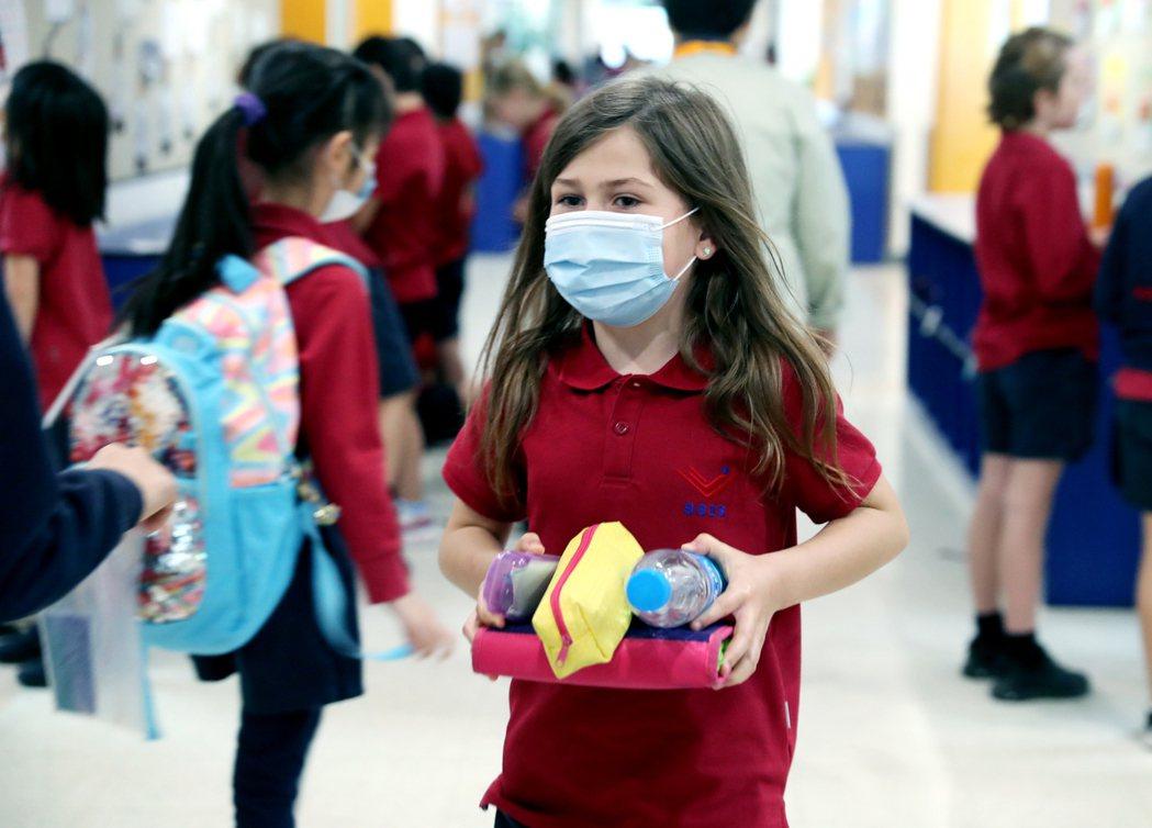 5月13日,蘇州新加坡國際學校780名外籍學生返校復課,一位返校的學生拿著學習用...
