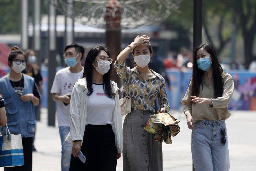 炎熱天氣長時間戴口罩,要注意補充水分攝取,防止中暑。示意圖/中新社