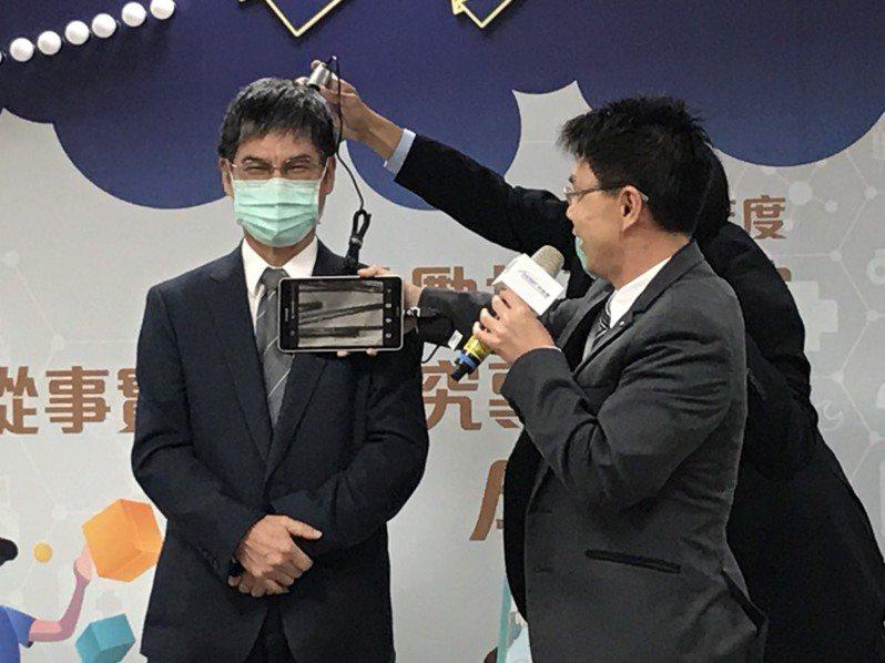南台科技大學電子工程系副教授張萬榮研發頭皮檢測系統,現場實測科技部長陳良基頭皮,發現非常健康。記者潘乃欣/攝影