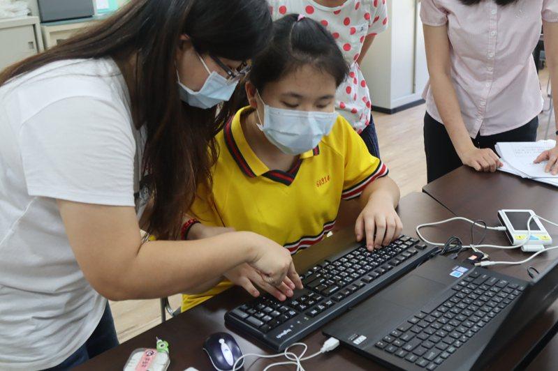 左營國中視障方姓女學生今午查考試場,試務人員指導她使用盲用電腦及擴視機等設備。記者王昭月/攝影