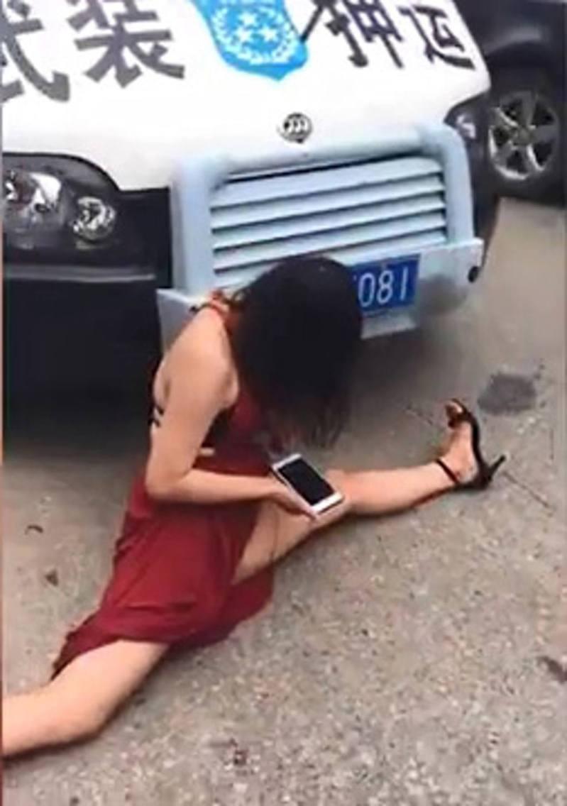 女子突破走出馬路做出一字腿攔下一輛運鈔車。(微博影片截圖)