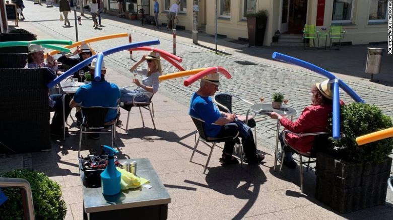 德國一家咖啡廳要求客人戴上裝有兩根交叉泡棉棒的草帽,以保持社交距離。圖擷自CNN