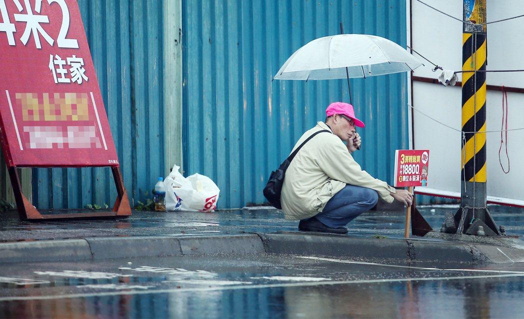 細雨紛飛的台北街頭,打工族左手撐傘、右手扶著房產廣告蹲低在人行道上。(圖/報系資...
