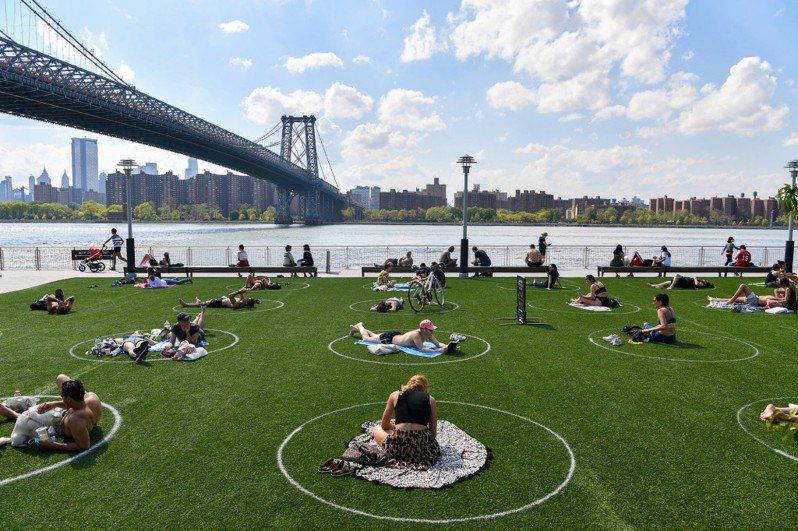 美國紐約布魯克林區的多米諾公園,為了讓市民在安全社交距離內還能外出活動,在大草皮上畫上白色圓框,民眾可以在屬於自己的白圈內自由活動。圖擷自New York Post