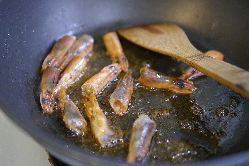 煮蝦膏,頭放入鍋中放入適量的食用油,起鍋加熱,稍作翻攪到鍋中出現蝦子的紅色。