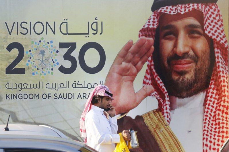 分析師認為,沙國王儲雄心勃勃的改革計畫已因新冠疫情及油價崩跌而停頓。圖為行人經過沙國吉達市一個購物中心外的看板,看板人物即王儲薩爾曼。美聯社