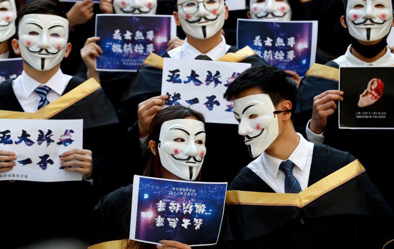 香港理工大學學生去年11月在畢業典禮前戴面具抗議。路透