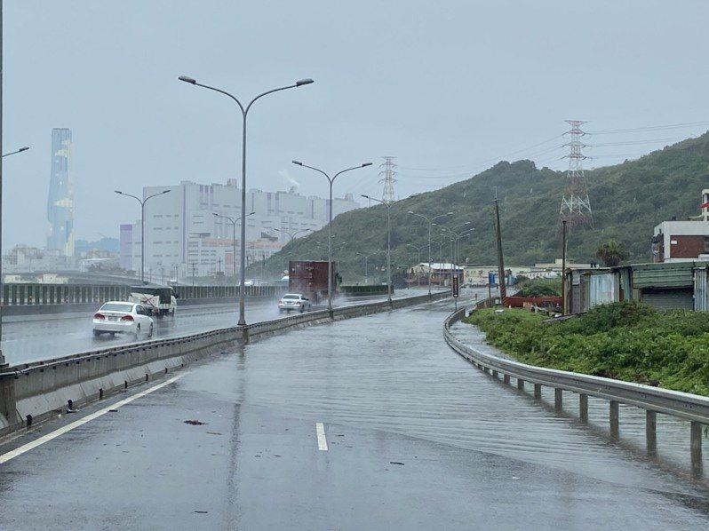 新北市今天近午驟降大雨,接近林口發電廠的台15線西濱公路慢車道開始積水。圖/警方提供