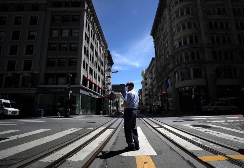美聯準會主席鮑爾認為,可能要到2021年底,美國才能從新冠肺炎疫情的衝擊中完全恢復。圖為一名美國郵差5月15日站在舊金山市一個街口。法新社