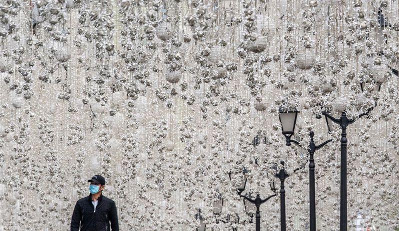 一名男子17日戴口罩走在莫斯科一條裝飾彩燈的街上。(法新社)