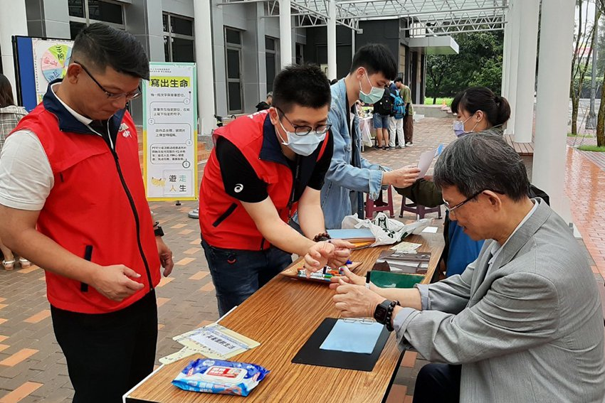 明新科大校長林啟瑞(右)出席生命教育推廣活動,參加用手腕夾筆寫卡片關卡,體驗身障...