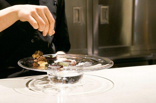 東京ESqUISSE CINq甜點店內,甜點師將盤子作為畫布,為客人準備甜點。(...