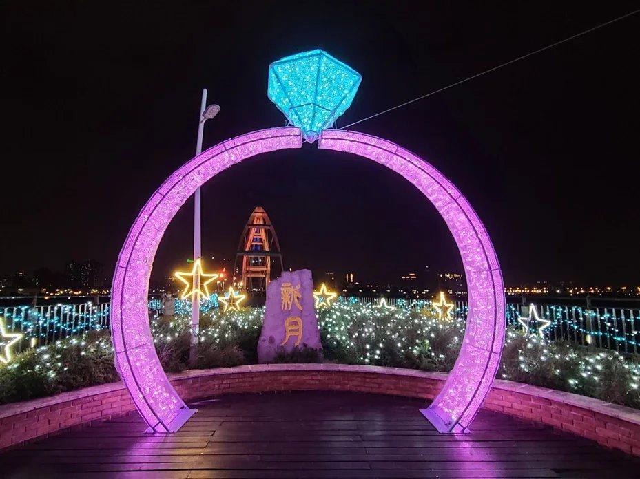 新北市府在新月橋舉辦幸福光雕展覽,結合裝置藝術及仿真月球,並設置1層樓高的鑽戒布...