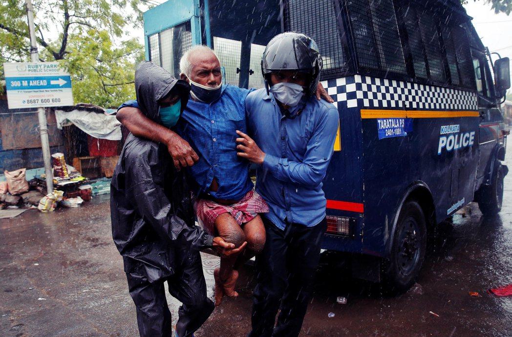 加爾各答警方,協助一名身心障礙者撤離。 圖/路透社