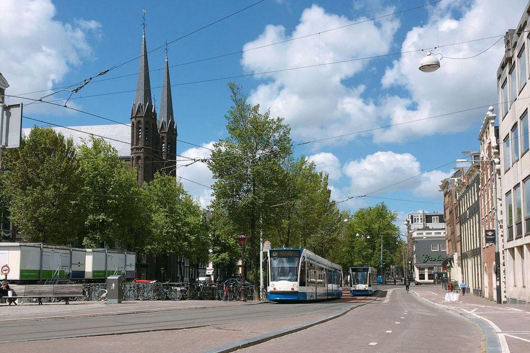 雖然沒有硬性封城鎖國,但阿姆斯特丹街頭幾乎不見人跡,遊客、腳踏車、汽車和電車交錯...