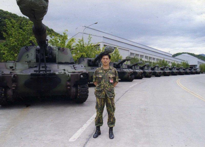 黃俊麟2002年與參與產製的M109砲車與勇虎戰車合影。 圖/黃俊麟提供