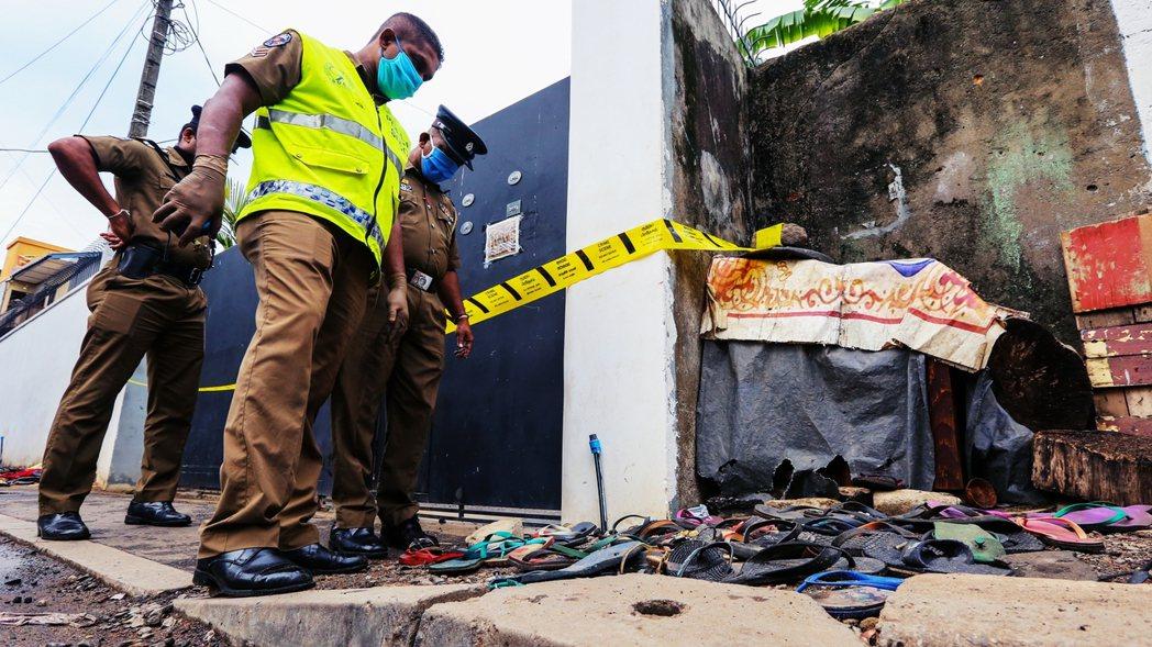 圖為21日死亡事故現場,可見許多拖鞋仍散落在倉庫前。 圖/歐新社