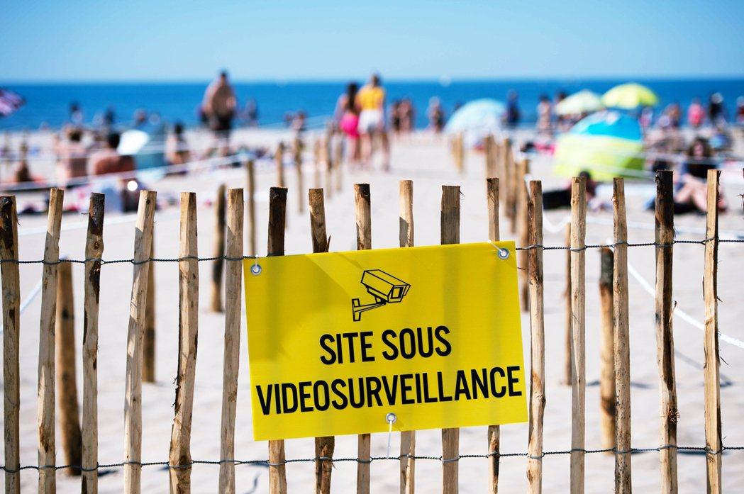 海灘上有寫著「監視器拍攝中」的警告示牌,提醒民眾盡責防疫。 圖/法新社