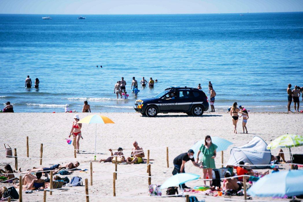 在日落沙灘上,一共有66個用繩子與木棍圍繞而成的四方形日曬區。 圖/法新社