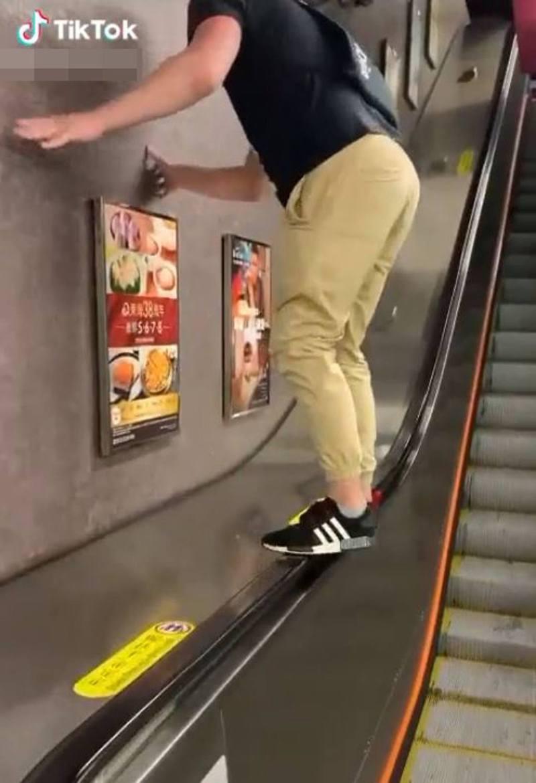 一名外國男子近日在港鐵車站內站在電梯的扶手上,遭大批網民怒轟。(抖音影片截圖)