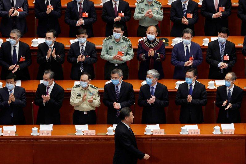 大陸全國政協十三屆三次會議廿一日在北京開議,大陸國家主席習近平(前中)在政協委員的掌聲中走進會場。(路透)