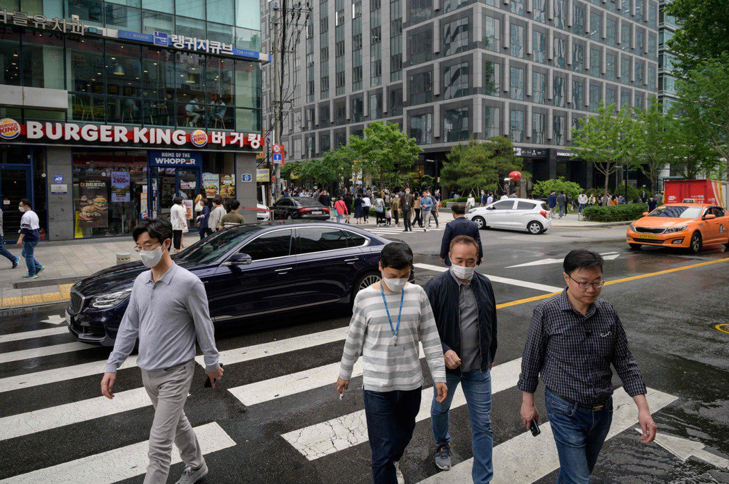 南韓目前進入生活防疫階段,圖為22日中午首爾上班族戴口罩出外用餐景象。法新社