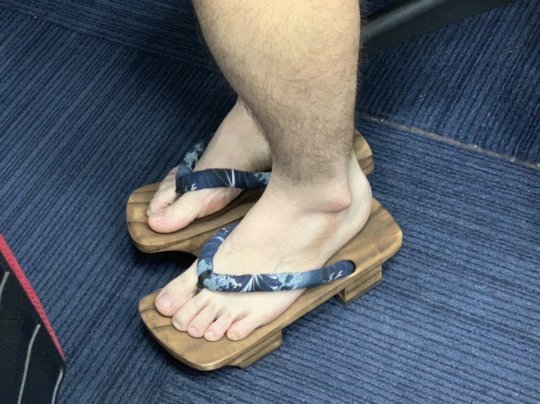 連日大雨,在外奔波的媒體記者,避免鞋被淋濕改穿木屐,被中央流行疫情指揮中心指揮官...