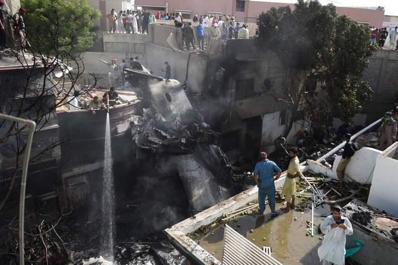 消防人員對失事的飛機殘骸灑水降溫。(法新社)