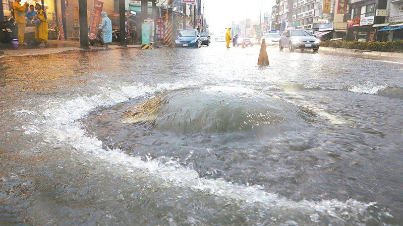 高雄市楠梓右昌路一帶積水嚴重,水壓衝開人孔蓋,車輛得涉水而過。記者劉學聖/攝影