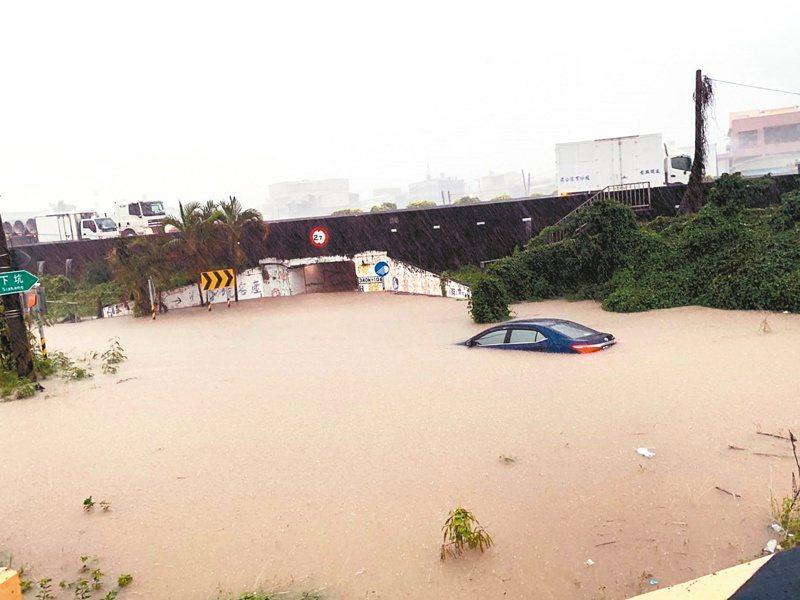 高雄市昨天大雨造成多處路段淹水,吳姓男子駕車行經路竹區太平路涵洞時拋錨,警方將吳男救出安置,但車輛被持續的雨勢淹至車頂。記者徐白櫻/翻攝