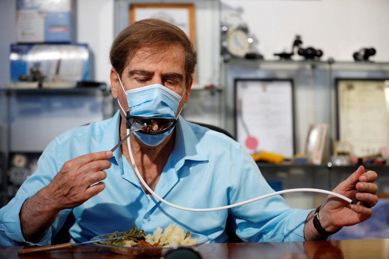 以色列一間公司按照腳踏車煞車的原理,開發用餐專用口罩。共同開發者吉特利斯(Meir Gitelis)親自展示如何手動開啟口罩用餐吃飯。路透
